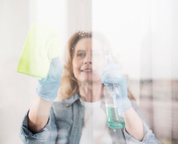Mulher sorridente, limpando a janela com pano Foto gratuita