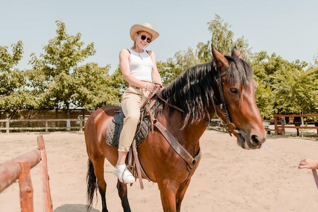 Mulher sorridente, montando, cavalo marrom, ligado, um, fazenda Foto Premium
