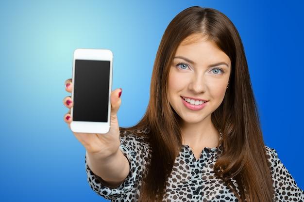 Mulher sorridente, mostrando a tela do smartphone Foto Premium