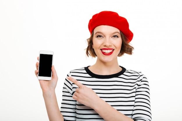 Mulher sorridente, mostrando a tela do telefone móvel Foto gratuita