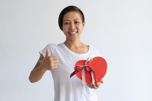 Mulher sorridente, mostrando, coração amoldou, caixa presente, e, polegar cima Foto gratuita