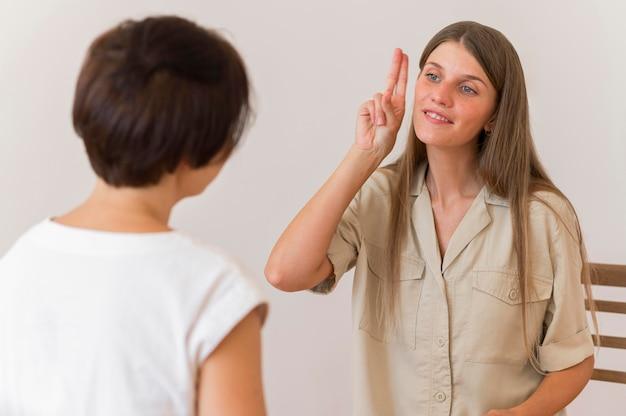 Mulher sorridente mostrando linguagem de sinais para outra pessoa Foto Premium