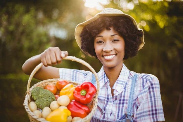 Mulher sorridente, mostrando, um, cesta, de, legumes, em, a, jardim Foto Premium