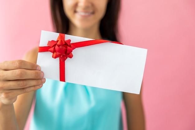 Mulher sorridente, mostrando um envelope Foto gratuita