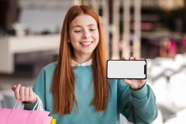 Mulher sorridente, mostrando um telefone simulado Foto gratuita