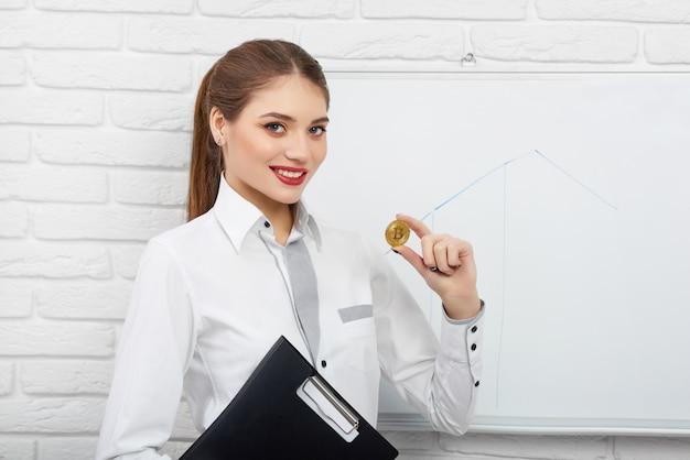 Mulher sorridente na blusa inteligente branca segurando bitcoin de criptomoeda perto de quadro de apresentação branco Foto Premium