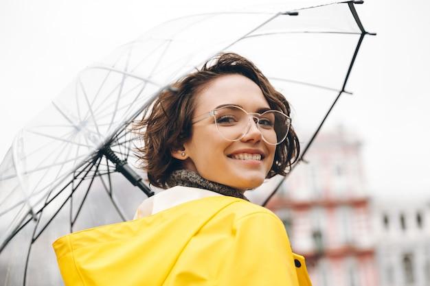 Mulher sorridente na capa de chuva amarela e óculos, tendo prazer em caminhar pela cidade sob o grande guarda-chuva transparente durante o dia chuvoso frio Foto gratuita