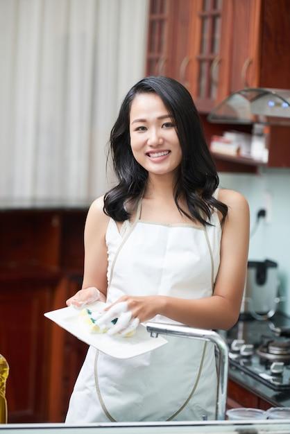 Mulher sorridente na cozinha lavando pratos Foto gratuita