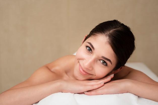 Mulher sorridente na mesa de massagem no spa Foto gratuita