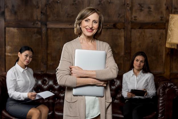 Mulher sorridente na reunião com o laptop Foto gratuita