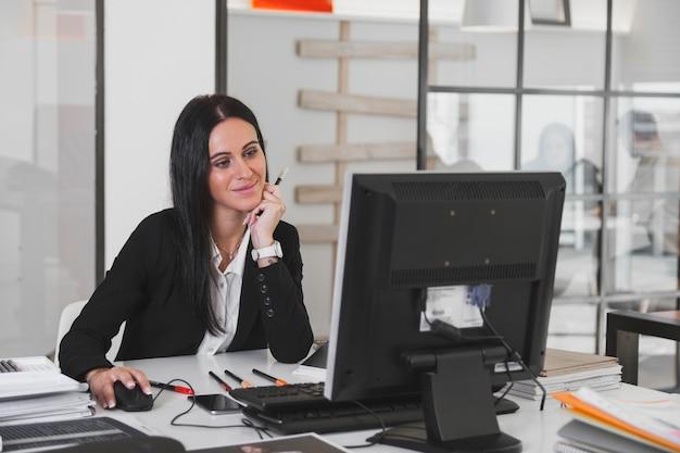Mulher sorridente no computador Foto gratuita