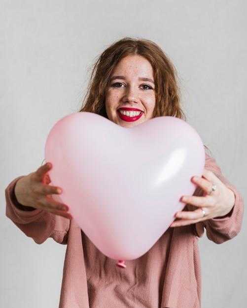 Mulher sorridente, oferecendo um balão Foto gratuita