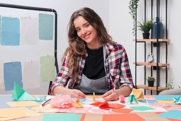 Mulher sorridente, olhando câmera, enquanto, fazendo, ofício Foto gratuita