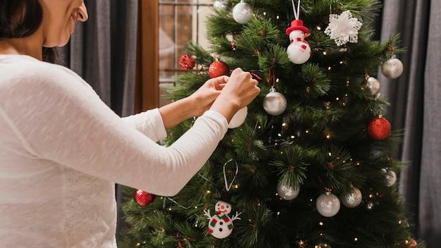 Mulher sorridente, organizando a bola branca na árvore de natal Foto gratuita