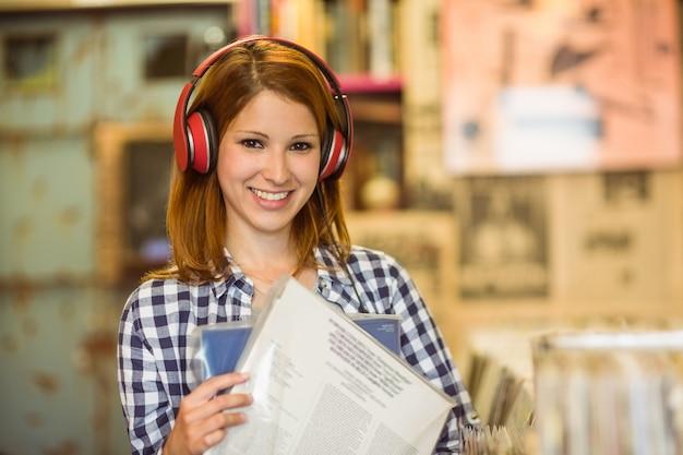 Mulher sorridente, ouvindo música e segurando vinis Foto Premium