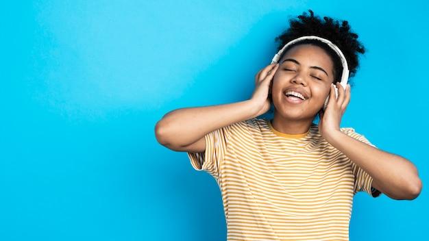 Mulher sorridente, ouvindo música em fones de ouvido Foto gratuita
