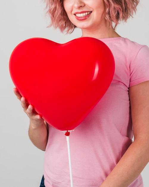 Mulher sorridente posando com balão Foto gratuita