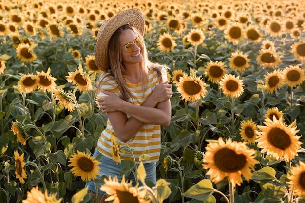 Mulher sorridente posando em campo de girassol Foto gratuita