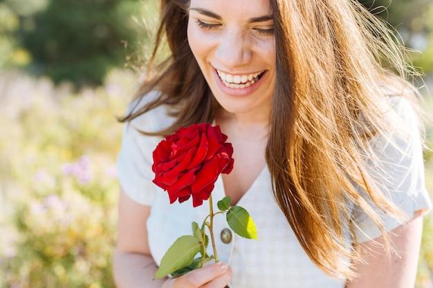 Mulher sorridente posando enquanto segura rosa Foto gratuita