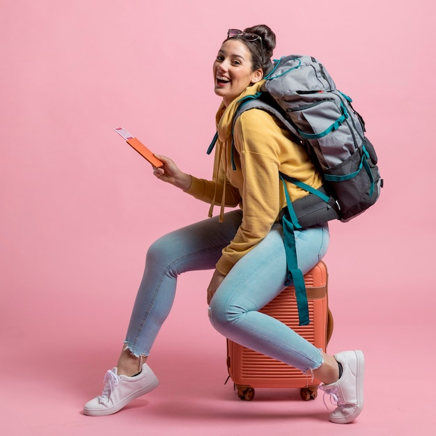 Mulher sorridente posando na bagagem Foto gratuita