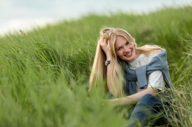 Mulher sorridente posando pela grama Foto gratuita