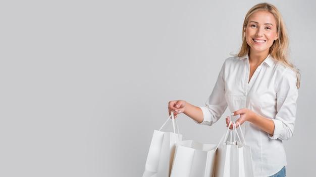 Mulher sorridente posando segurando sacolas de compras com espaço de cópia Foto gratuita