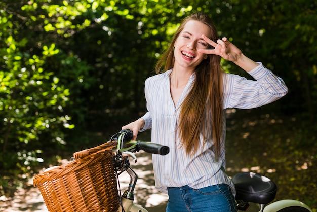 Mulher sorridente, posar, ligado, dela, bicicleta Foto gratuita