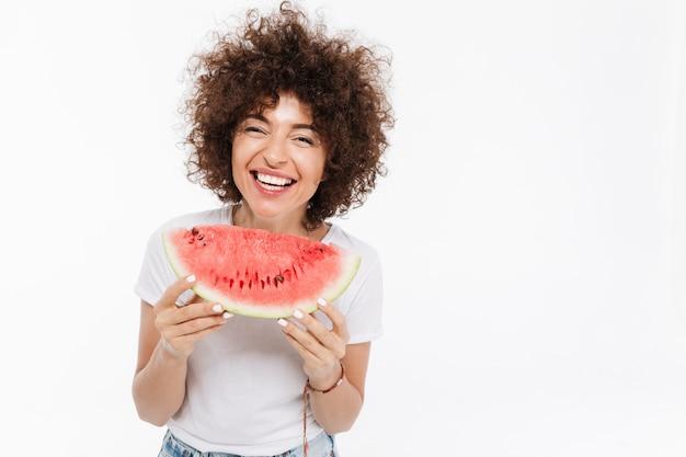 Mulher sorridente segurando a fatia de melancia e rindo Foto gratuita
