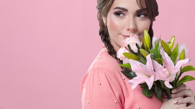 Mulher sorridente segurando buquê de lírios Foto gratuita
