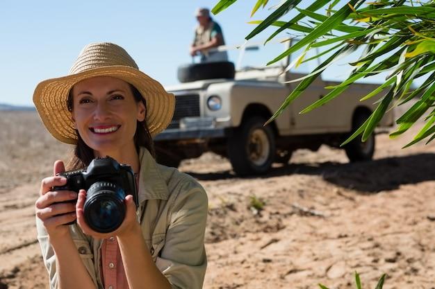 Mulher sorridente, segurando, câmera, com, desligado, veículo estrada Foto gratuita