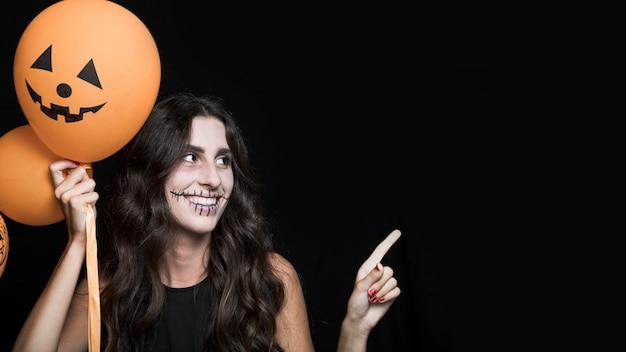 Mulher sorridente, segurando, dia das bruxas, balões Foto gratuita