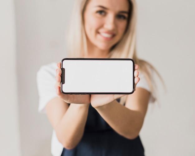 Mulher sorridente segurando o telefone com mock-up Foto gratuita