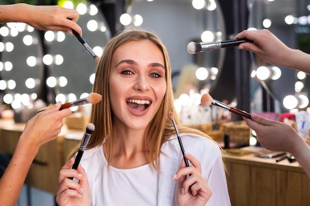Mulher sorridente segurando os pincéis de maquiagem Foto gratuita