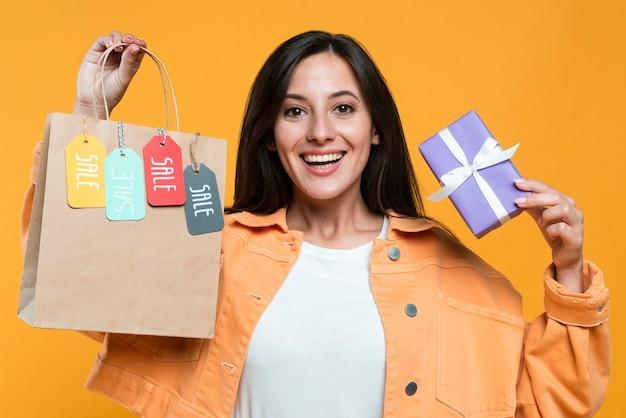 Mulher sorridente segurando sacola de compras com etiquetas e cartão de crédito Foto gratuita