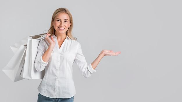 Mulher sorridente segurando sacolas de compras e exibindo espaço à esquerda Foto gratuita