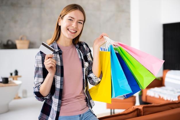 Mulher sorridente segurando sacos de papel e cartão de crédito Foto gratuita