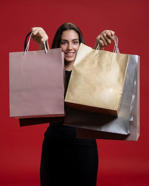Mulher sorridente segurando suas sacolas de compras Foto gratuita