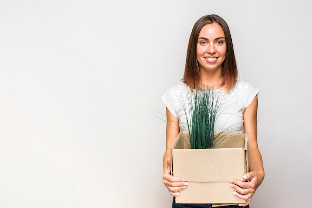 Mulher sorridente segurando uma caixa com copyspace Foto gratuita