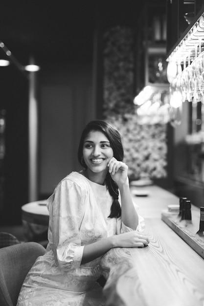 Mulher sorridente, sentando, em, barra, contador Foto gratuita