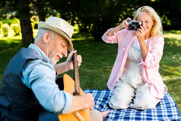 Mulher sorridente, tirando uma foto para um homem com uma guitarra Foto gratuita