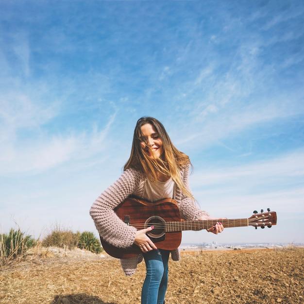 Mulher sorridente tocando guitarra na natureza Foto gratuita