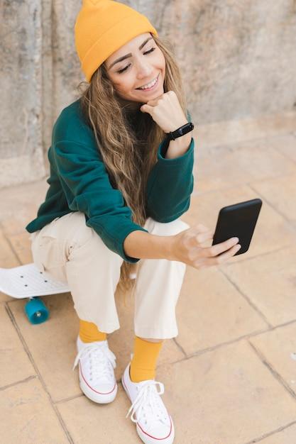 Mulher sorridente tomando selfie enquanto está sentado no skate Foto gratuita
