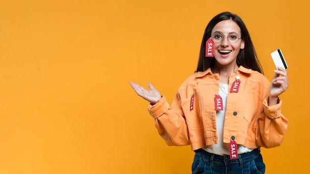 Mulher sorridente usando óculos com etiqueta de venda e segurando um cartão de crédito Foto gratuita