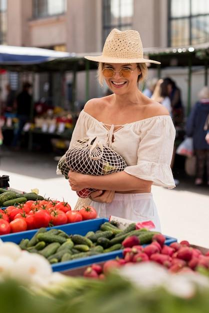 Mulher sorridente usando saco orgânico para vegetais Foto gratuita