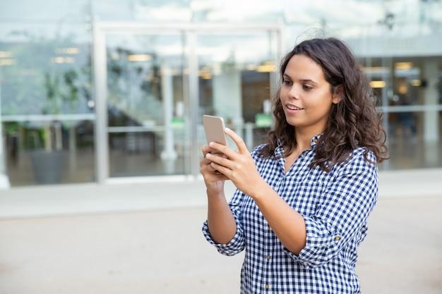 Mulher sorridente usando smartphone na rua Foto gratuita