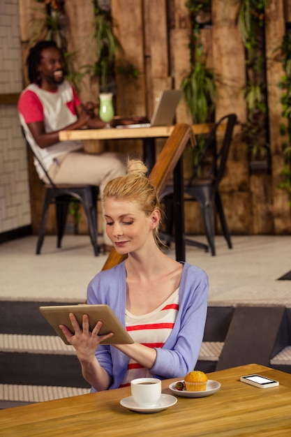Mulher sorridente usando um tablet Foto Premium