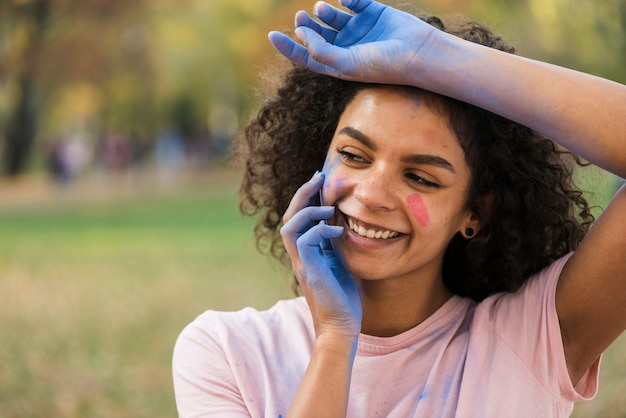 Mulher sorrindo com as mãos cobertas de pó azul Foto gratuita