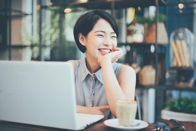 Mulher sorrindo com um café e um laptop Foto gratuita