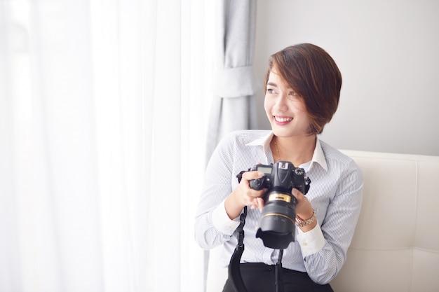 Mulher sorrindo com uma câmera reflex Foto gratuita