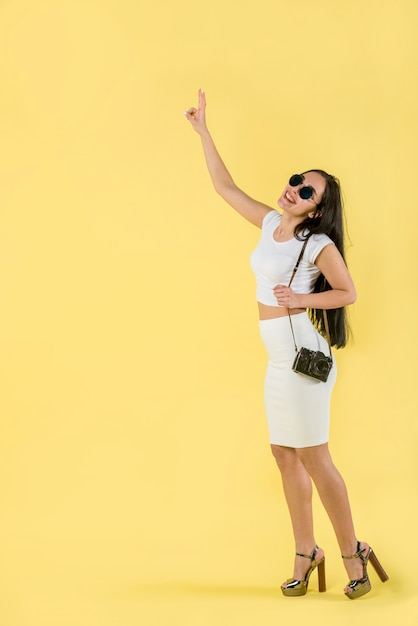 Mulher sorrindo e apontando os dedos para cima Foto gratuita